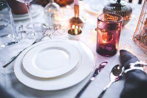 Mesa con platos, cubiertos y velas.