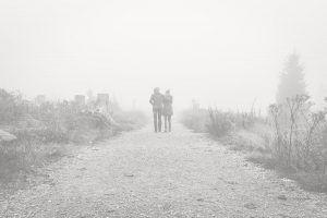 Pareja caminando abrazados entre la niebla