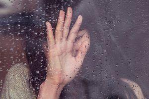 Mujer triste junto a la ventana