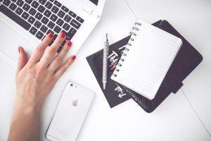Mano junto a un cuaderno y dispositivos electrónicos