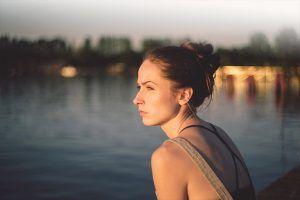 Mujer pensativa al lado de un río
