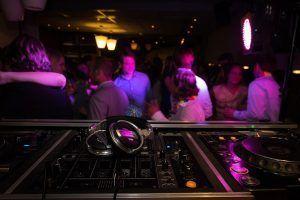 Mesa de mezclas en un local nocturno con gente divirtiéndose