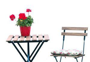 Una mesa con un jarrón rojo y una silla a su lado
